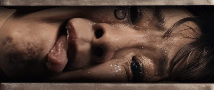 The sideways face of a woman's head being squeezed in a Vise grip. A contact has popped out and lays upon her face and her tongue is out