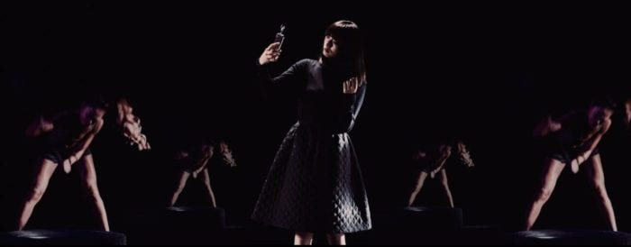 A woman dressed in black twirls her long dark hair in her left hand while taking a selfie with her right. In The background four women in a V pattern swing sledgehammers