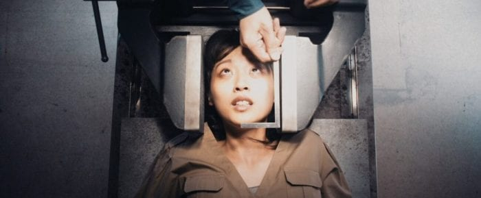 A girl lying on a metal slab and her head between two clamps looks anxiously at a hand hoovering above her, measuring her face.