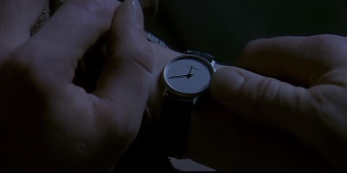 David turning Nicole's watch back, holding her arm with both his hands, in Fear