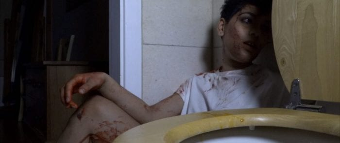 A woman in a t-shirt covered in blood is shadowed by the toilet she sits beside.