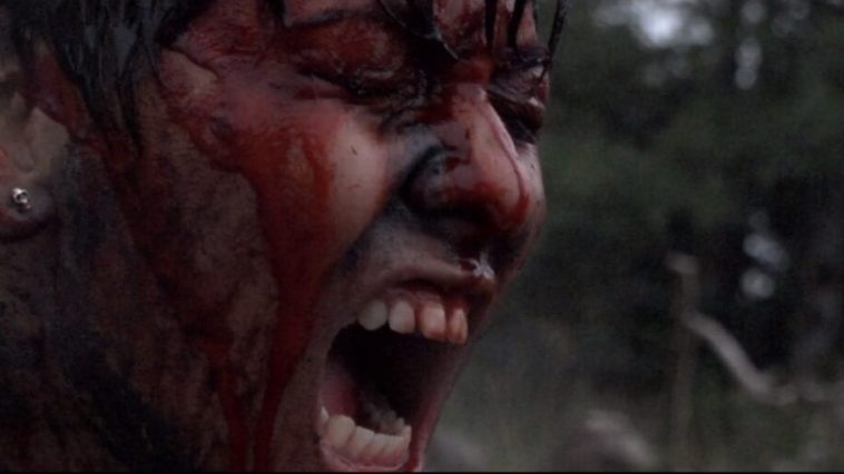 A woman's face is close up. She's in a field her face is strained, screaming as hard as she can. She's covered in blood and paint.
