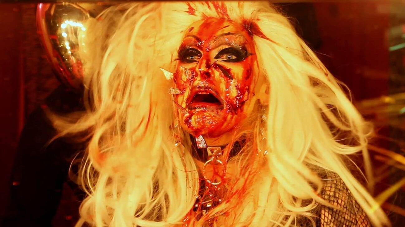 Audrey Heartburn (Paul Bohn) with shards of mirror in her face, bloodied up and gasping.