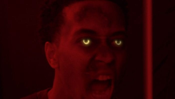 A man with glowing yellow eyesin red lighting strains in a yelling motion toward the camera