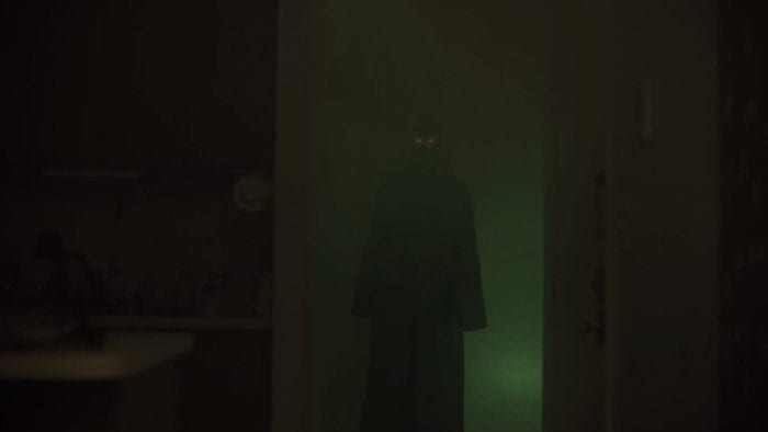 a looming figure with glowing eyes stands in a doorway at the other end of a foggy hallway