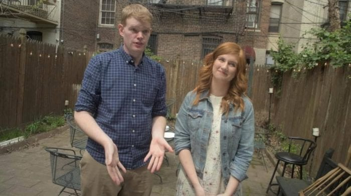 A tall sandy haired man in a button down shirt and khaki pants stands with his arms outstretched in front of him next to a smiling red-haired woman in a denim jacket and a flowery sundress.