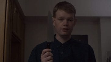 An expressionless man holds a knife