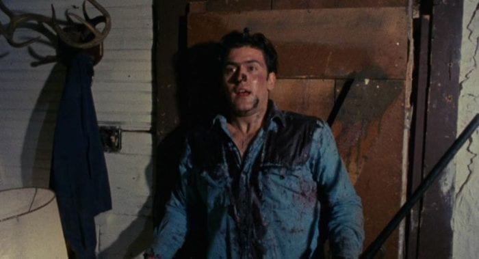 Ash leans wearily against a door, covered in blood.