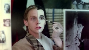 a young man sits and paints his face exactly down the middle. One half remains the image of the boy with sandy hair, the other half painted white with jet black hair resembling a vampire.