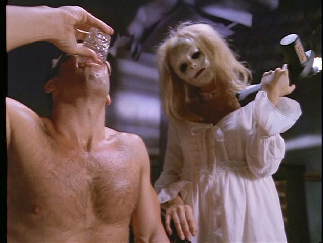 A shirtless Peter Onorati takes a shot of gin while a baby doll faced woman in a white nightgown cocks her head menacingly while holding an electric saw