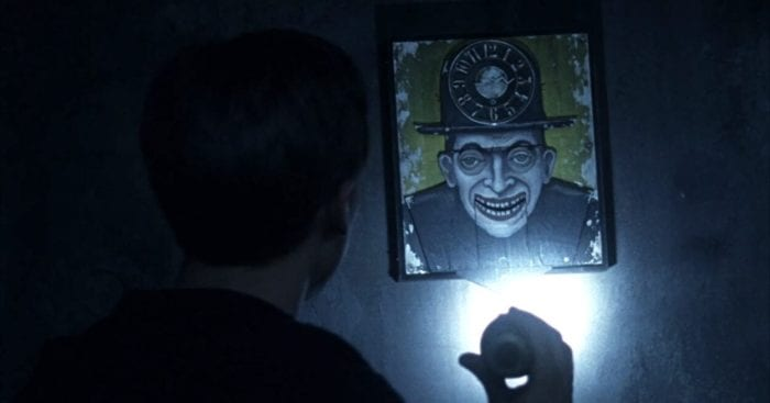 Danny shines a light on a menacing painting of a man with sunken eyes and a wide sinister grin, a working clock is contained in the man's bowler hat