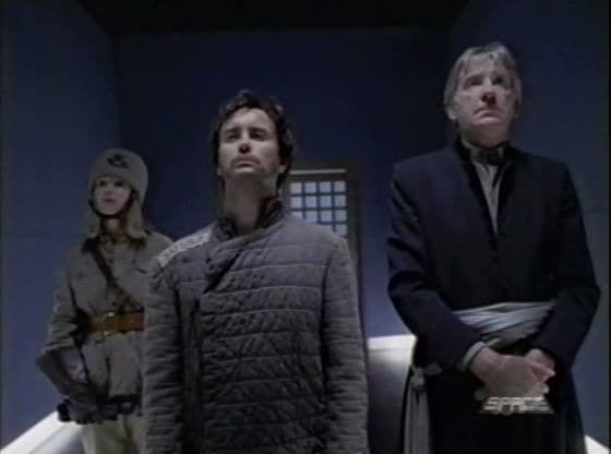A Soviet dressed female guard stands holding a gun down at her side in the background while 50557 (Jeffrey Combs) stands chest out and chin held high beside his suit wearing doctor (David Warner)