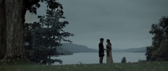 A large tree fills the left side of the picture and a slightly smaller one on the right, a lake in the background as Percy and Mary stand hand in hand on the grassy bank in the foreground