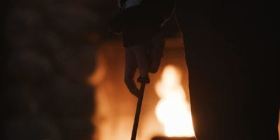A hand holds a fire poker menacingly in front of a roaring fireplace.
