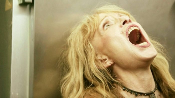An older woman with flowing blonde hair has her back to a large industrial freezer. She's looking up and screaming with a terrorized look on her face.