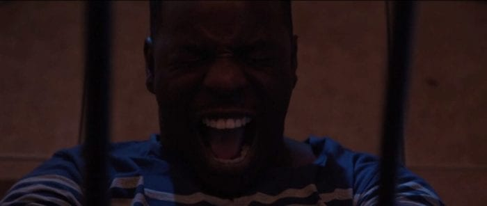 A Man laying on the floor releases a full scream betwen two bars in front of his face.