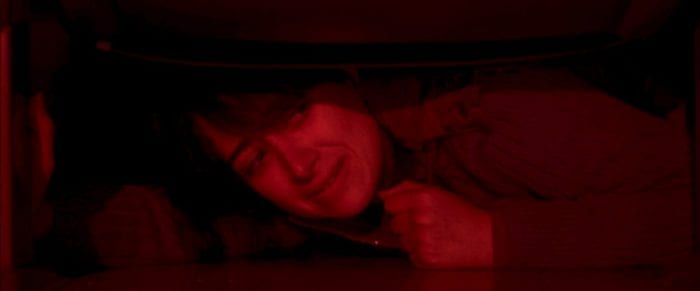A woman's hair covers half her face as she cowers under a theater seat in red lighting