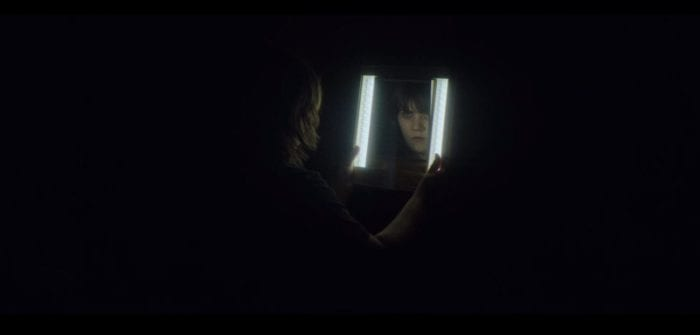 Catherine stares into a brightly lit mirror while the mirrored face stares back toward the camera.