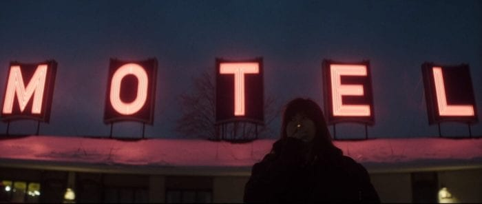 "Catherine stands outside in a heavy winter jacket smoking a cigarette. A neon sign reads ""MOTEL"" on the roof's overhang above her."