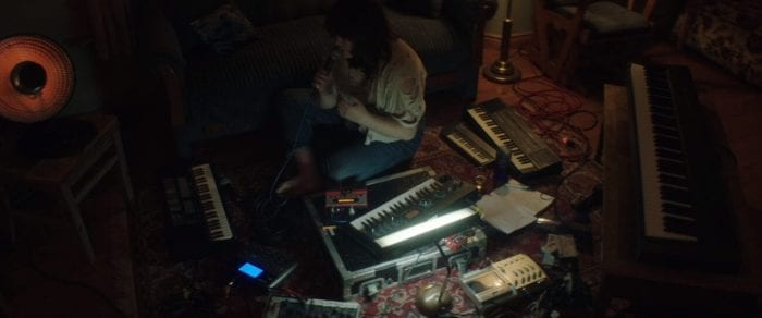 Catherine sits on the floor surrounded by various instruments, cords and electronic equipment.