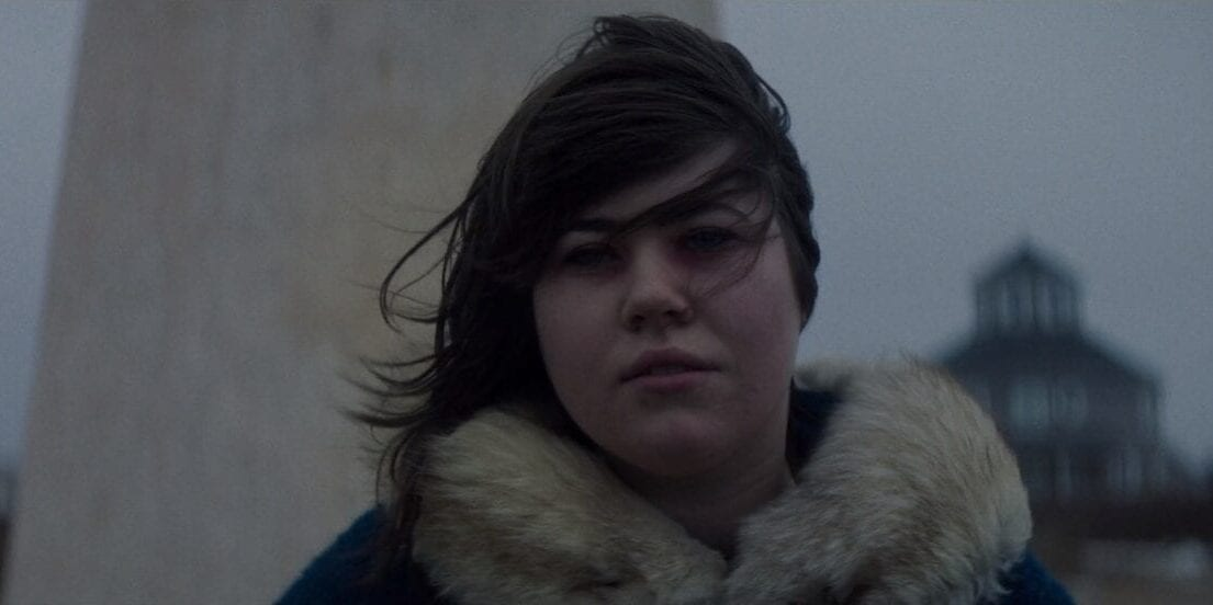 Catherine stands in a heavy winter coat, her hair blown across her face. A large structure just behind her and a large beach house over her left shoulder.