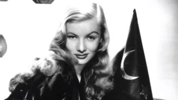 Veronica Lake stares into the camera over her right shoulder against a white backdrop with a witch's hat adorning a half moon on it.