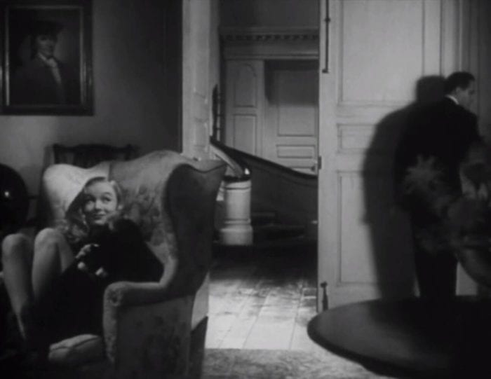 Veronica Lake sits in a chair smiling and petting her black cat while Frederic March investigates the room's light switch