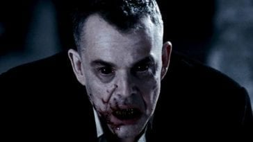 Marlow in a dark coat, eyes black and his mouth is smeared with the blood of his victim