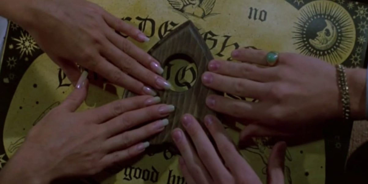 Four hands touching the planchette of a ouija board.
