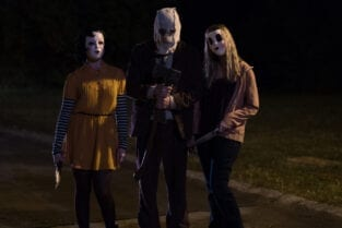 Three masked figures stand in the dark holding weapons.