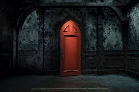 Angular red door stands ajar in dark, creepy room.