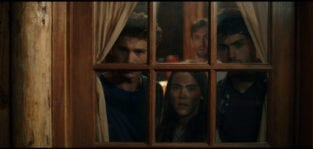 Four teenagers stare cautiously out from the inside of a cabin window.