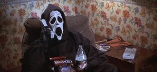 Costumed figure wearing ghostface mask talks into phone and drinks a forty oz bottle of beer.