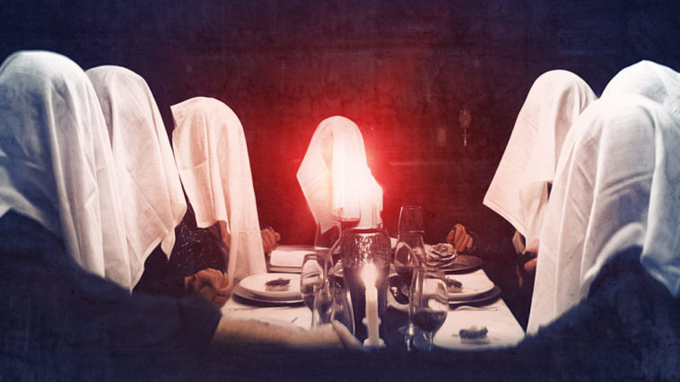 The Sinclairs sit at a dining room table holding hands with their napkins over their head and an orb of red light floating from the center of the feast