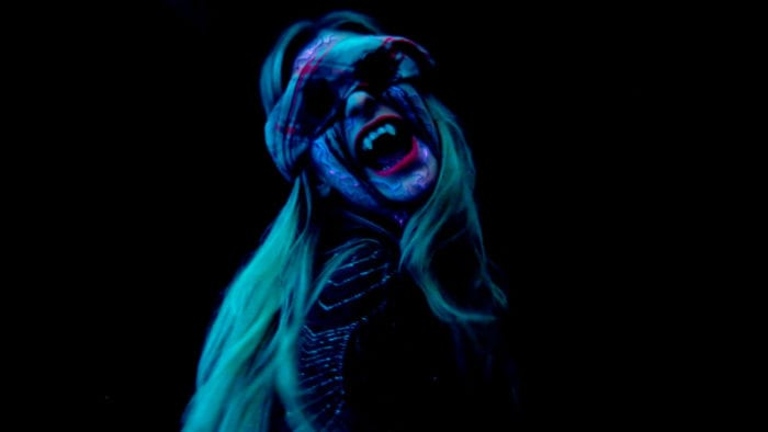 A female member of the Sinclair family has her eyes carved out and is wearing a blood soaked towel over her eyes and exposing her fangs in an odd florescent glow