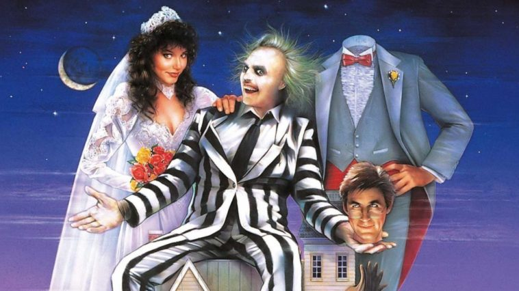 Beetlejuice, played by Michael Keaton, sitting on a house with Barbara Maitland, played by Geena Davis, on the left, and holding the head of Adam Maitland, played by Alec Baldwin, on the right, with the headless Adam standing on the right.