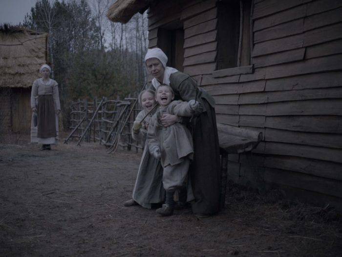 A mother holds onto her two young children, outside of their log cabin. They are all wearing period clothing.
