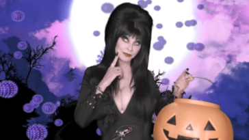 Elvira, Mistress of the Dark (Cassandra Peterson), looks thoughtful while holding a large jack-o-lantern trick-or-treat bucket.