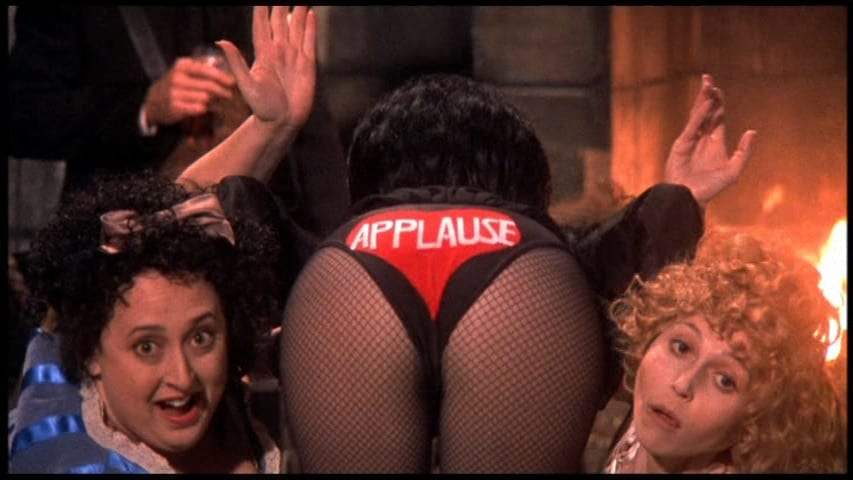 """Elvira, Mistress of the Dark (Cassandra Peterson), showing underwear that says, """"Applause"""" on it, with Zou Zou (Mary Jo Smith) and Lady Roxana Hellsubus (Heather Hopper) on either side of her, in the film, """"Elvira's Haunted Hills"""" (2001)."""