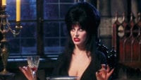 Cassandra Peterson as Elvira, Mistress of the Dark, sits at a dinner table, unhappy with what's going on.