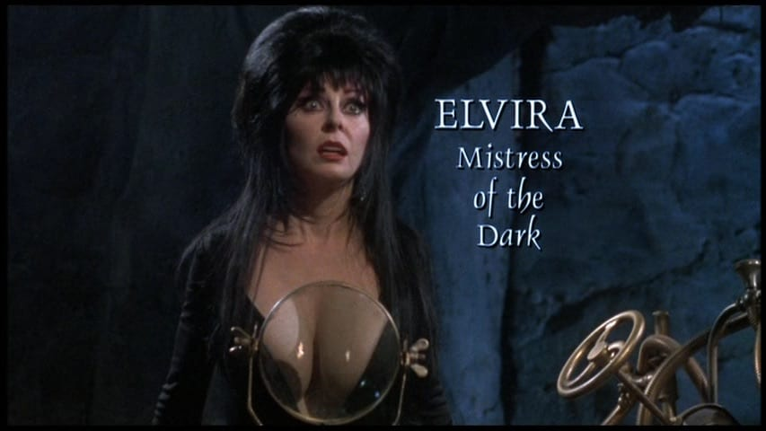 """Cassandra Peterson as Elvira, Mistress of the Dark, her chest enlarged by a magnifying glass, from the 2001 film, """"Elvira's Haunted Hills."""""""