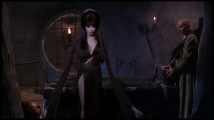 "Elvira, Mistress of the Dark (Cassandra Peterson), with cartoonishly long arms, in the film, ""Elvira's Haunted Hills"" (2001)."
