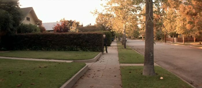 A suburban sidewalk in autumn, shaded in the slowly setting sun. Michael Myers, wearing a painted William Shatner mask and a dark jumpsuit, is peering out in the distance from behind a bush.