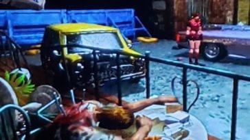 Claire wanders the desolate streets of Raccoon City. Surrounded by destruction and death. A man is dead slumped over at a table.
