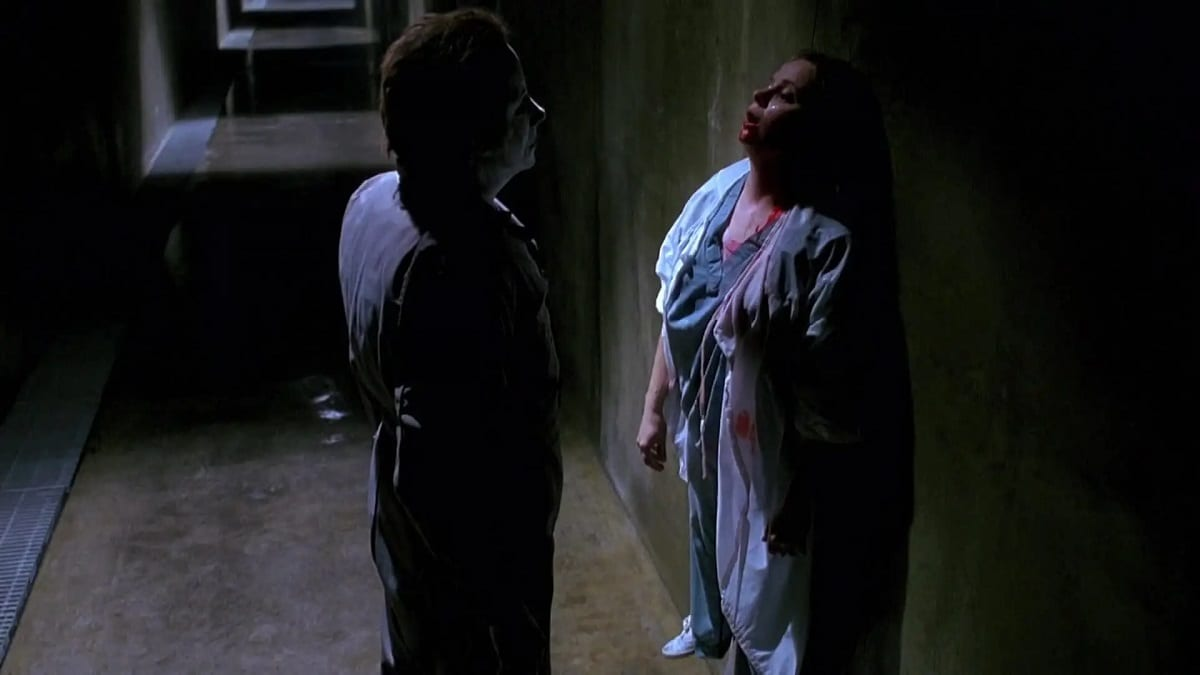 Michael stands and stares at his recent kill as she's attached to the wall, very much dead.