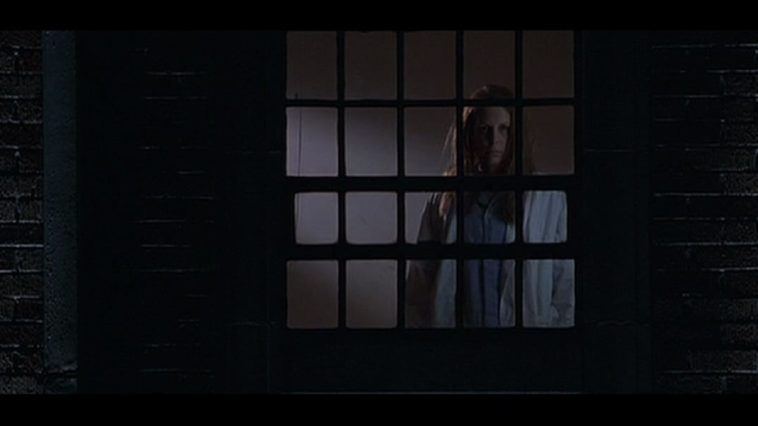 Jamie Lee Curtis looks out her window in the night while standing inside.