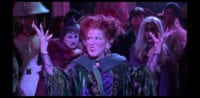 """Winifred Sanderson (Bette Midler) begins to sing, """"I Put a Spell on You,"""" in the middle of a crowd, with her sisters Mary (Kathy Najimy) and Sarah (Sarah Jessica Parker) behind her, in the film """"Hocus Pocus"""" (1993)."""