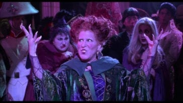"Winifred Sanderson (Bette Midler) begins to sing, ""I Put a Spell on You,"" in the middle of a crowd, with her sisters Mary (Kathy Najimy) and Sarah (Sarah Jessica Parker) behind her, in the film ""Hocus Pocus"" (1993)."
