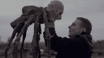 A man holds up a spider body with a man's head.