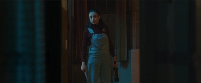 Leni stares down a hallway wearing overalls and holding a knife and a bottle of wine.